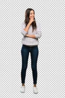Een volledige lengte shot van een jonge spaanse brunette vrouw op zoek naar de kant