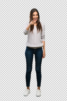 Een volledige lengte shot van een jonge spaanse brunette vrouw verrast en wijst naar voren