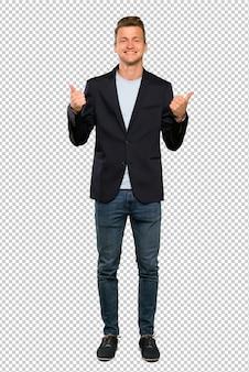 Een volledige lengte shot van een knappe blonde man met thumbs up gebaar en glimlachen