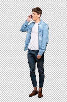Een volledige lengte shot van een knappe jongeman een gesprek met de mobiele telefoon te houden