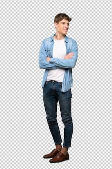 Een volledige lengte shot van een knappe jongeman met armen gekruist en gelukkig