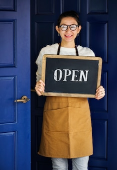Een vrolijke kleine bedrijfseigenaar met open teken