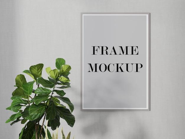 Eenvoudig grijs muurframe mockup naast groene plant 3d visualisatie