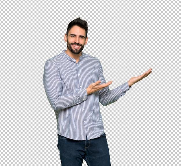 Elegante hombre con camisa extendiendo las manos hacia un lado para invitar a venir.