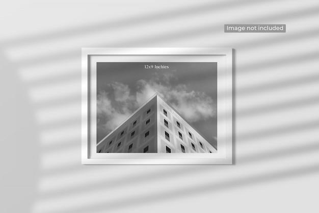 Elegante maqueta de marco de fotos minimalista colgada en la pared