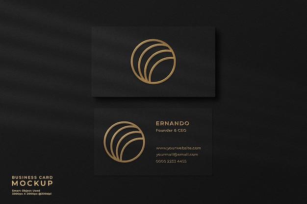 Elegante maqueta de tarjeta de visita negra con lámina dorada con efecto de relieve y sombra