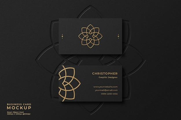 Elegante maqueta de tarjeta de visita negra con lámina de oro con efecto de relieve y logotipo de tipografía en el fondo