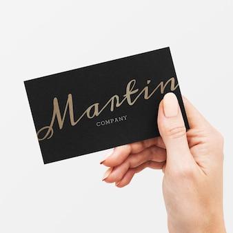 Elegante tarjeta de visita en negro y dorado en una mano.