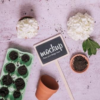 Elementos de jardinería con maqueta de pizarra pequeña.