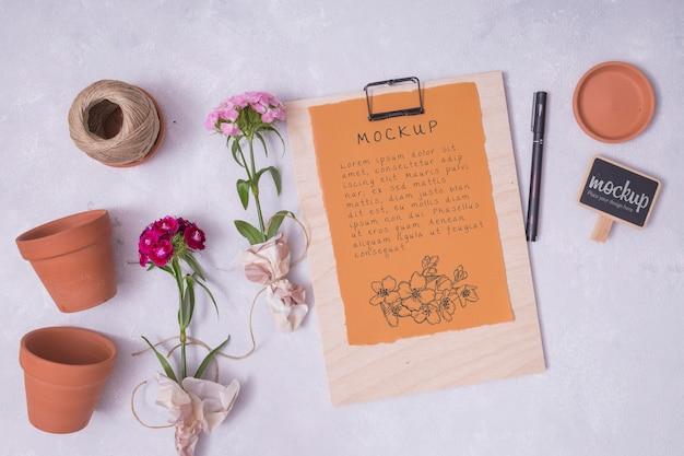 Elementos de jardinería planos laicos con maqueta de portapapeles