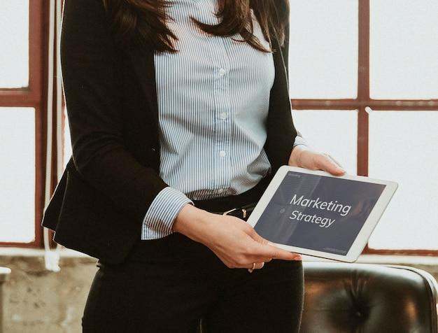 Empresaria discutiendo la estrategia de marketing con una maqueta de tableta
