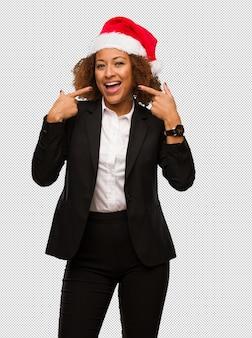 La empresaria negra joven que lleva un sombrero de santa de la navidad sonríe, señalando la boca