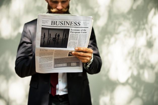 Empresario de pie y leyendo el periódico