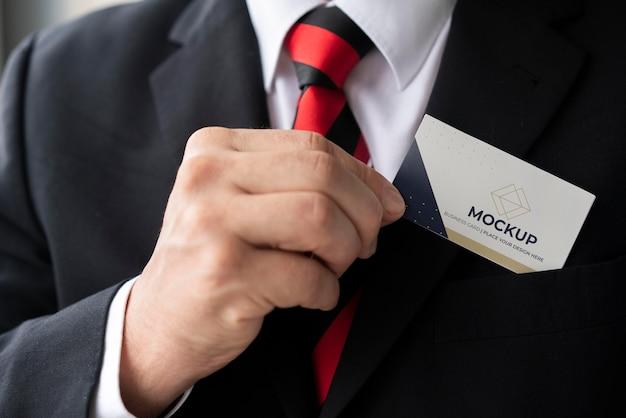 Empresario de primer plano poniendo maqueta de tarjeta de visita en su bolsillo