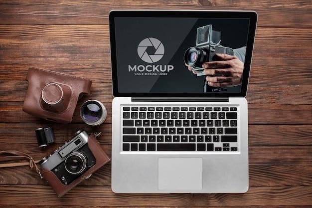 Endecha plana del espacio de trabajo de madera del fotógrafo con ordenador portátil