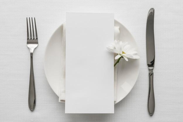 Endecha plana de la maqueta del menú de primavera en un plato con cubiertos y flor