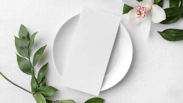 Endecha plana de maqueta de menú de primavera con plato y flor