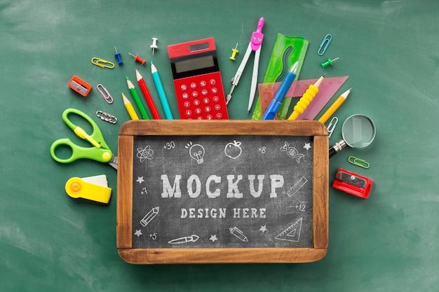 Endecha plana de pizarra con elementos esenciales de la escuela para el día de la educación