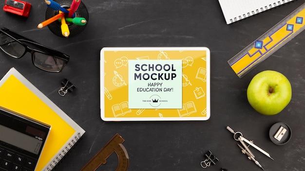 Endecha plana de tableta con elementos esenciales de la escuela para el día de la educación
