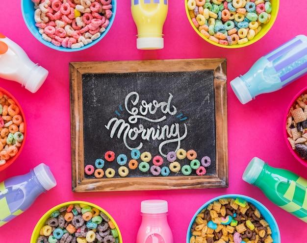 Endecha plana de tazones de cereal y botellas de leche sobre fondo rosa