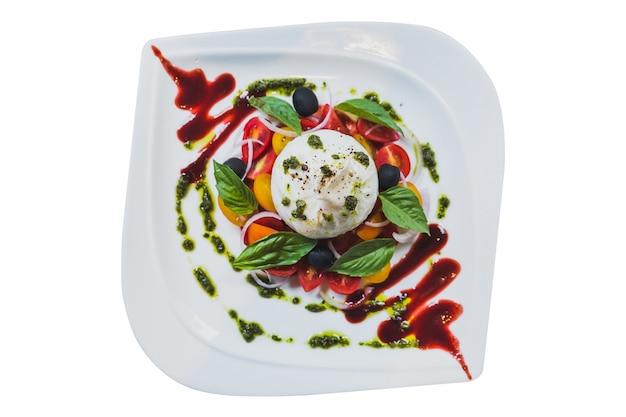 Ensalada aislada de queso burrata que incluye rodajas de tomate, cebolla, uva, hojas de albahaca.