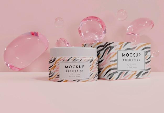 Envase de crema y burbujas rosas