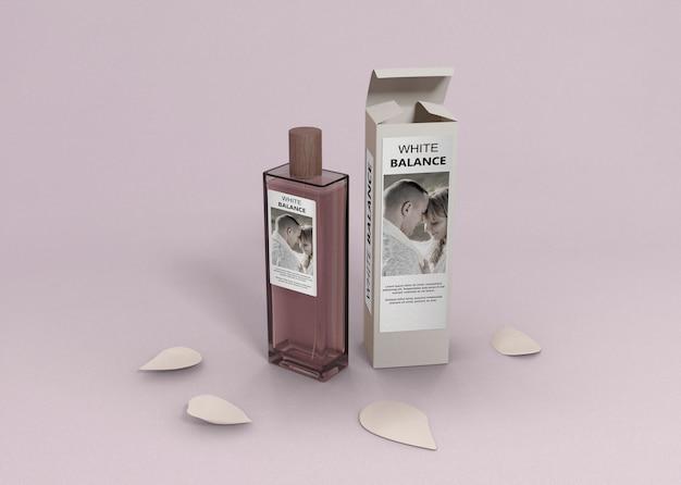 Envase de perfume en mesa con pétalos