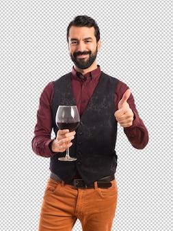 Equipaggi il panciotto da portare che tiene un vetro di vino