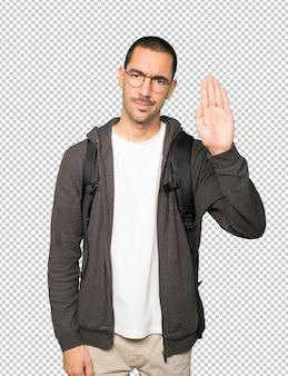 Ernstige student die een stopgebaar maakt met zijn handpalm