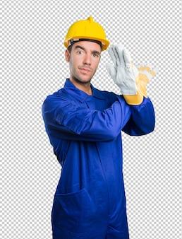Ernstige werkman die een gebaar van verbod op witte achtergrond doet