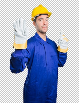 Ernstige werkman met een eindegebaar op witte achtergrond