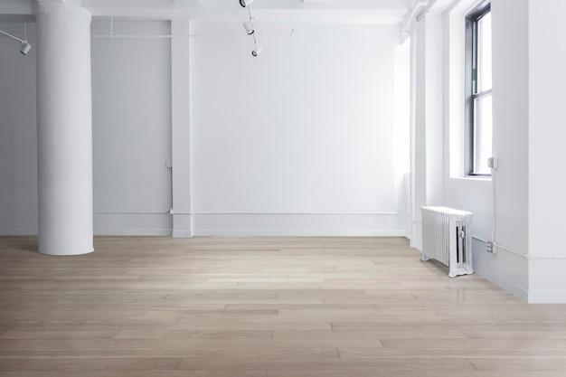 Escena de habitación vacía con paredes blancas y suelo de parquet