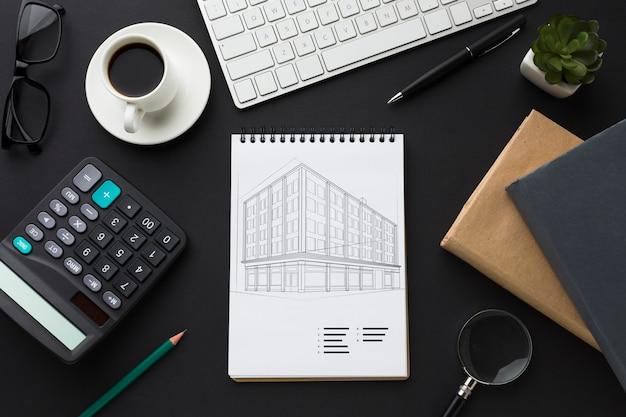 Escritorio de oficina con calculadora, maqueta de café y cuaderno