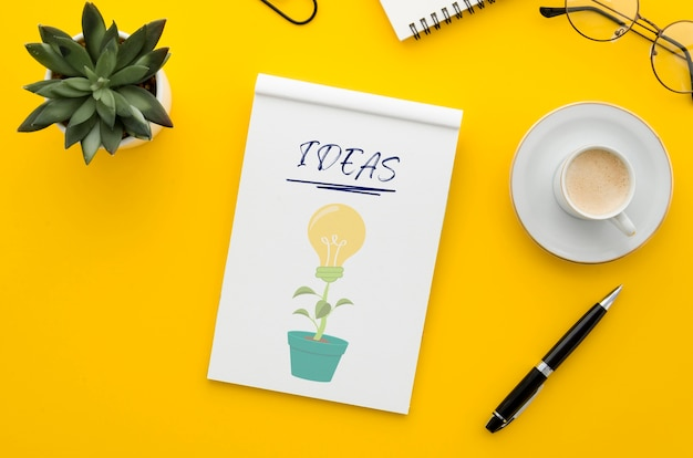 Escritorio de oficina con maqueta de café y cuaderno