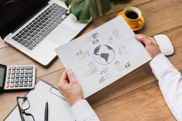 Escritorio de oficina con persona sosteniendo maqueta de hoja de papel