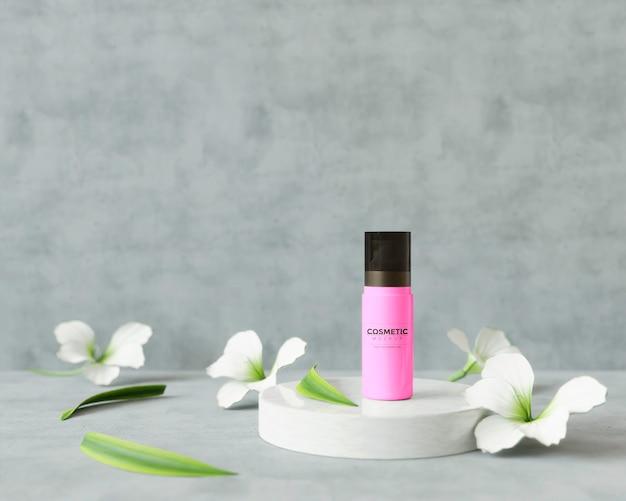 Esmalte de uñas rosa sobre un soporte con flores
