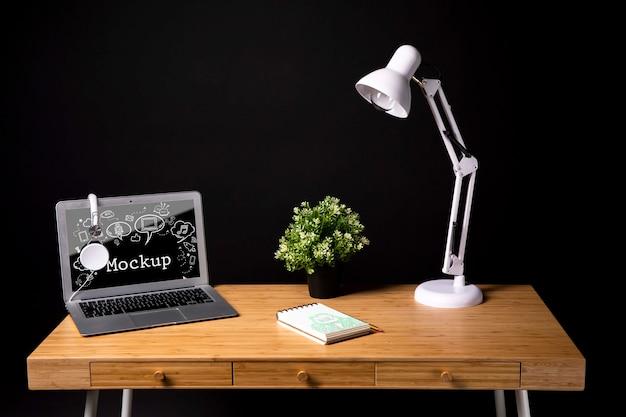 Espacio de trabajo con lámpara y planta.