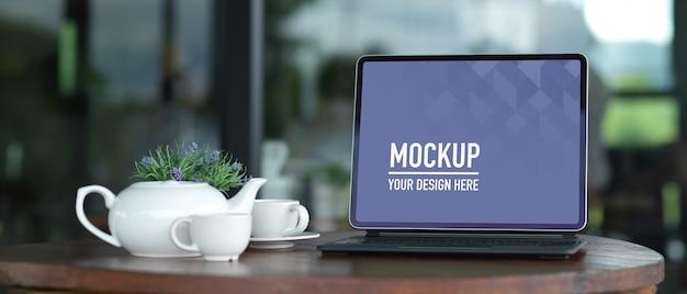 Espacio de trabajo con tableta de pantalla en blanco de maqueta con teclado con tetera de cerámica en la mesa de madera