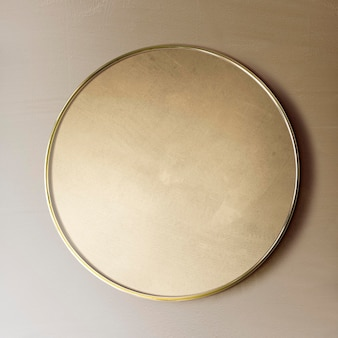 Espejo con marco dorado en una maqueta de pared marrón