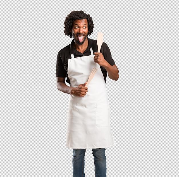 Espressione di fornaio americano africano bello di fiducia ed emozione, divertente e amichevole, mostrando la lingua come un segno di gioco o divertimento