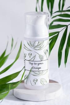 Espuma de afeitar blanca o maqueta de botella de loción de limpieza en una mesa de mármol con hojas de palma de hoja perenne