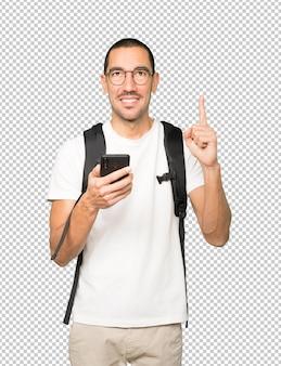Estudiante feliz apuntando hacia arriba y usando un teléfono móvil