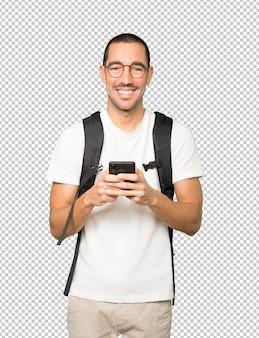 Estudiante feliz usando su teléfono móvil
