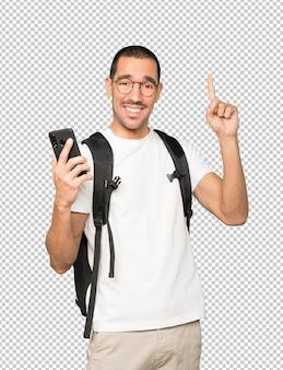 Estudiante feliz usando un teléfono móvil y apuntando hacia arriba