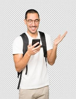 Estudiante sorprendido apuntando y usando su teléfono móvil