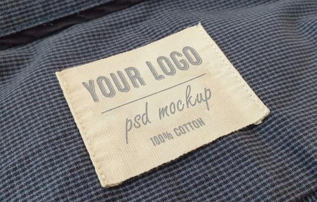 Etiqueta de etiqueta de maqueta de logotipo en relieve en la textura de la tela