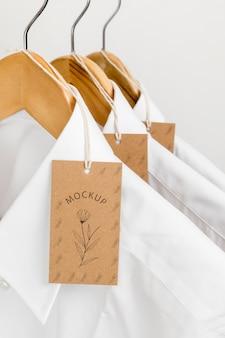 Etiquetas de precio ecológicas y camisas formales con maqueta de perchas