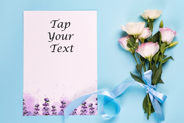 Eustoma flores con hoja de papel en una vista azul, superior.