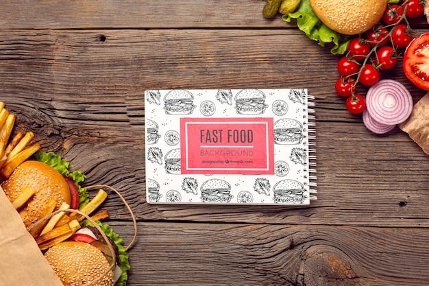 Fast food e verdure su fondo di legno