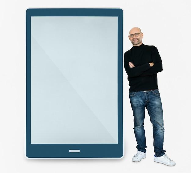 Felice uomo in piedi accanto a un tablet
